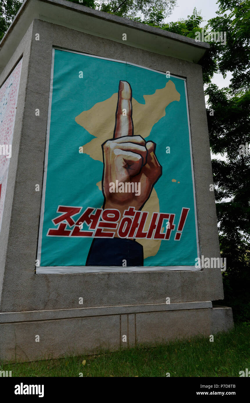 Poster on the North Korea side of the DMZ showing a single finger, one country, reunification being the aim. - Stock Image