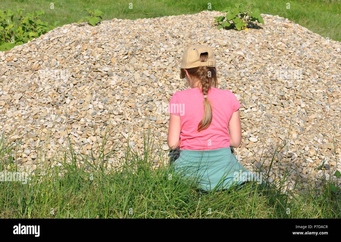 Blonde child girl, (7-9) standing with her back in front of a heap (pile) of stones and playing, copy space - Stock Image