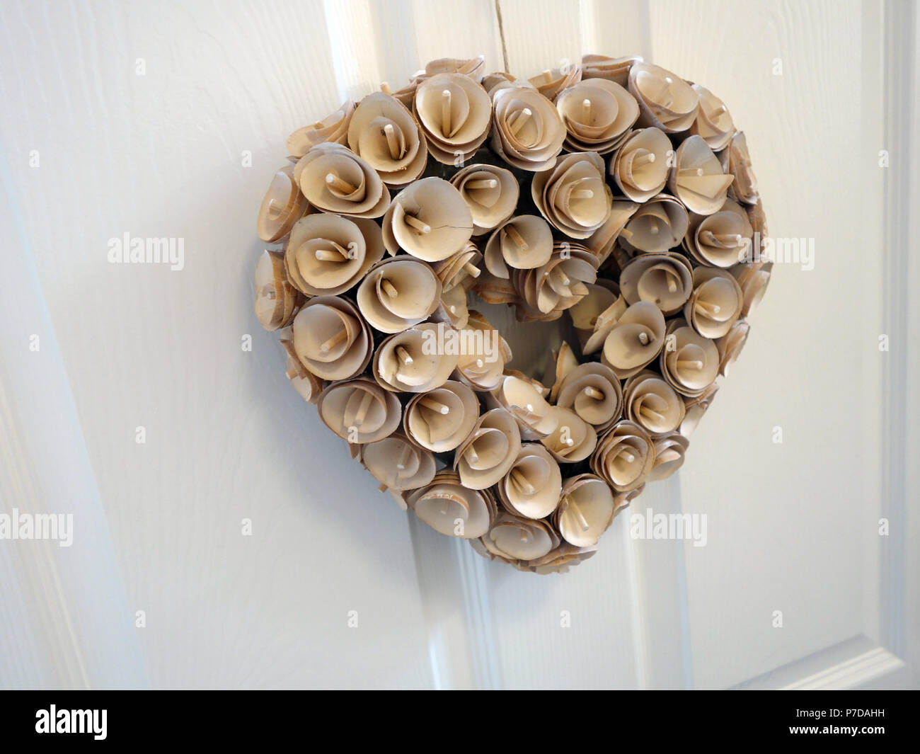 Carved wooden flowers formed into heart shape for door hanging - Stock Image