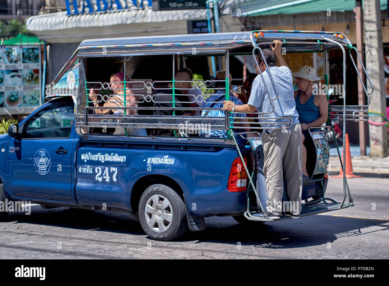 Fully loaded Songthaew taxi car Thailand with passengers riding on the tailgate platform - Stock Image