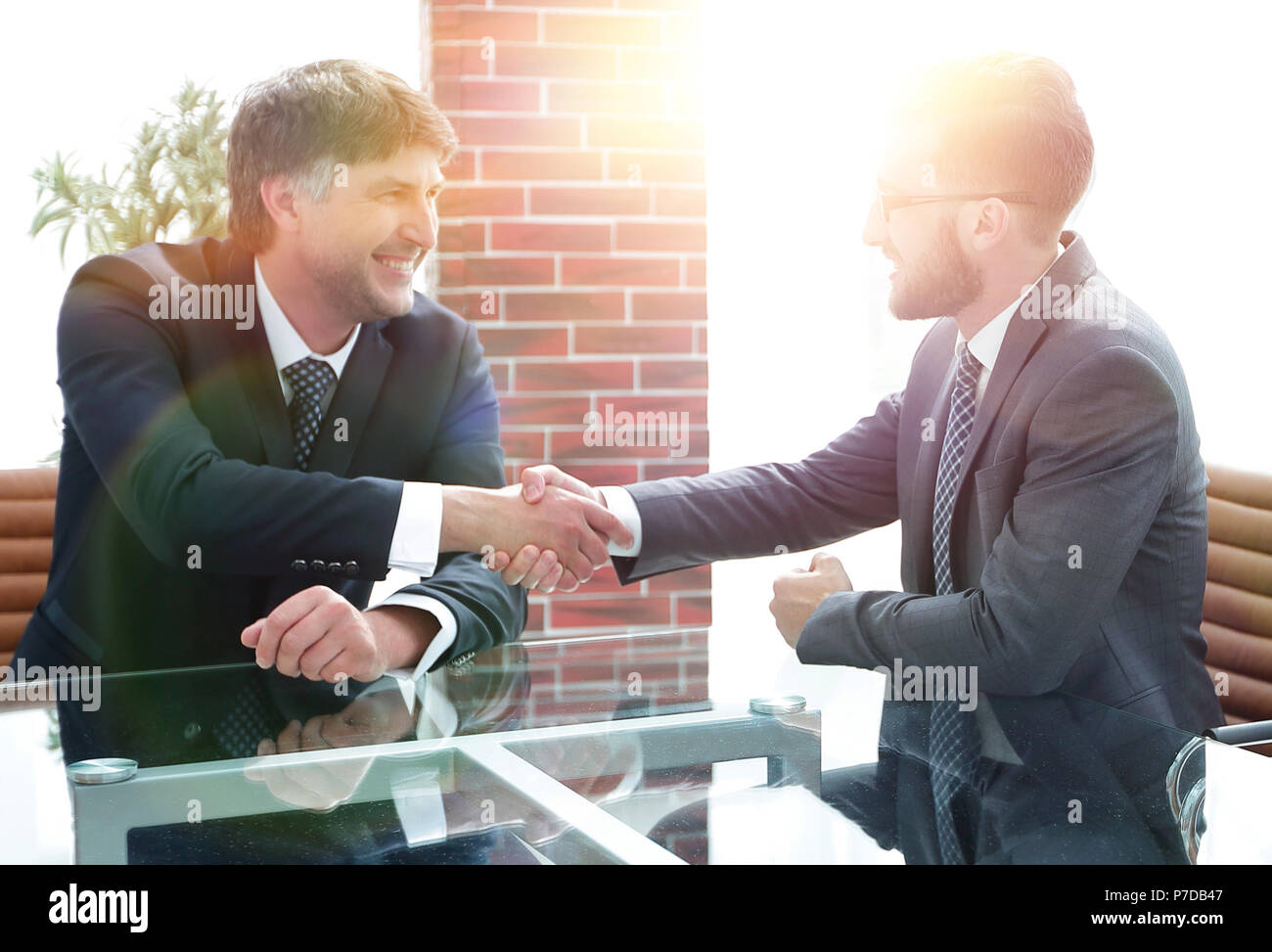 Business partners shake hands after discussing the contract - Stock Image