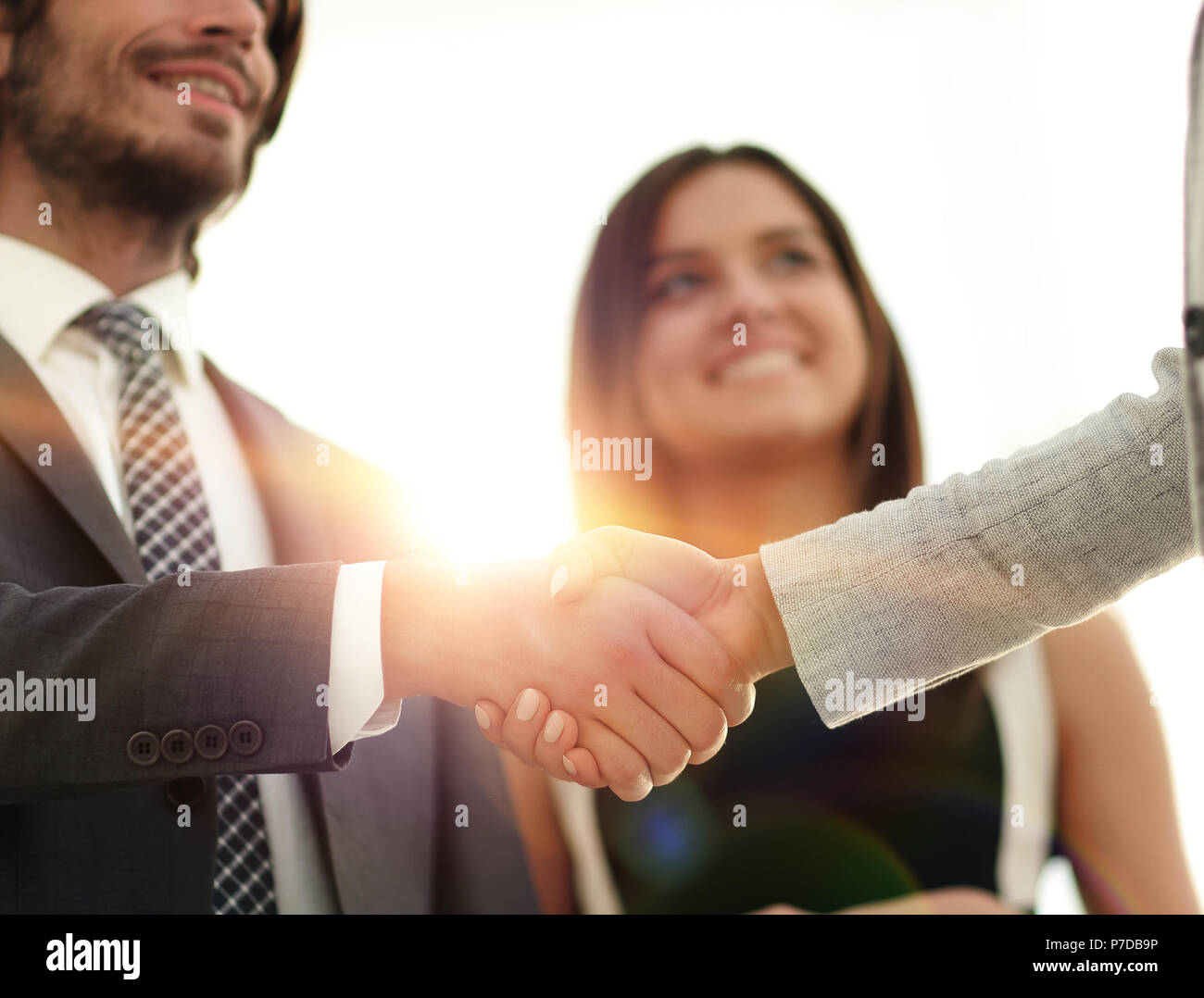Businesspeople  shaking hands against room with large window loo - Stock Image