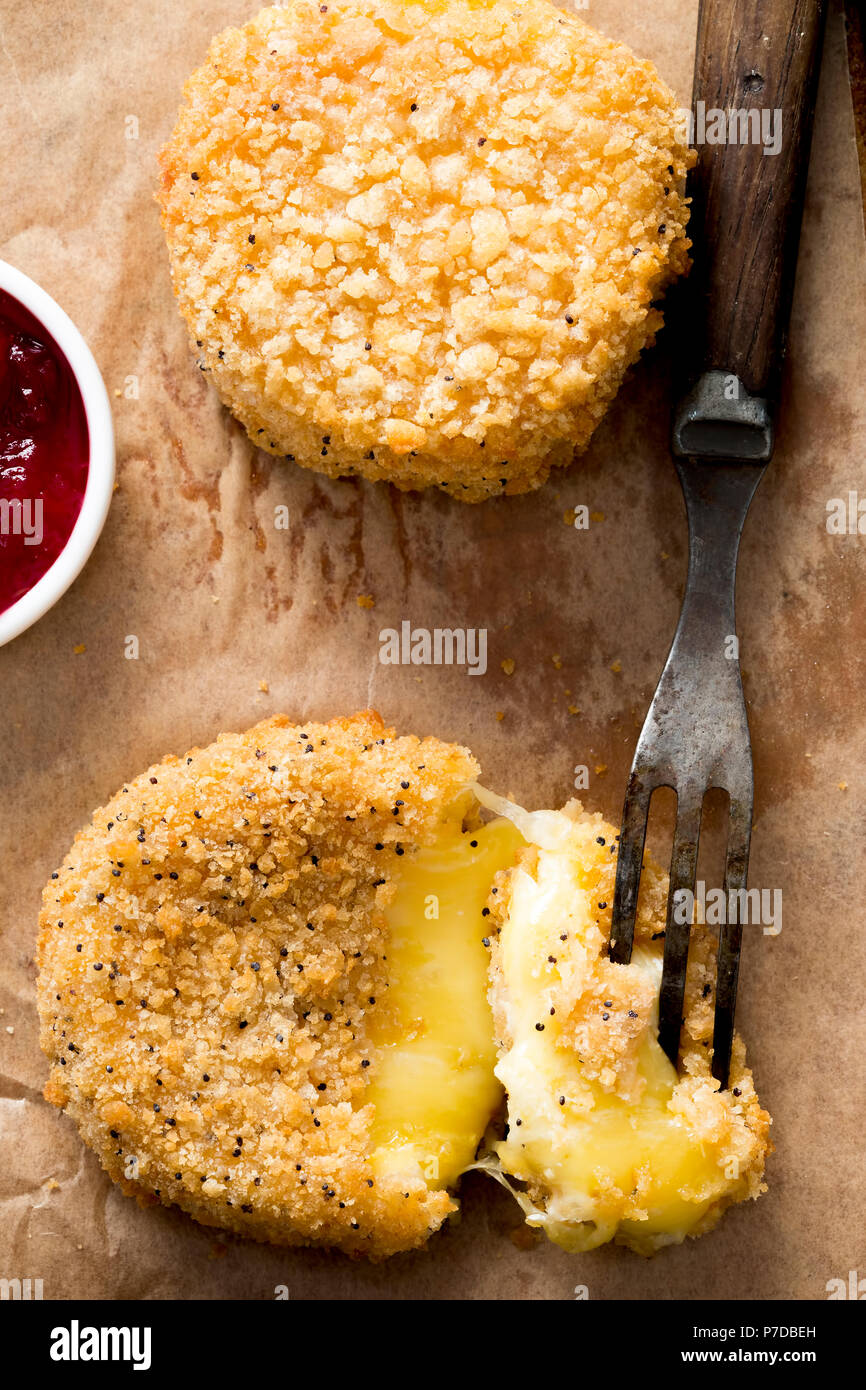 Fried camembert in golden poppy seed breadcrumb, with cranberry& apple sauce - Stock Image