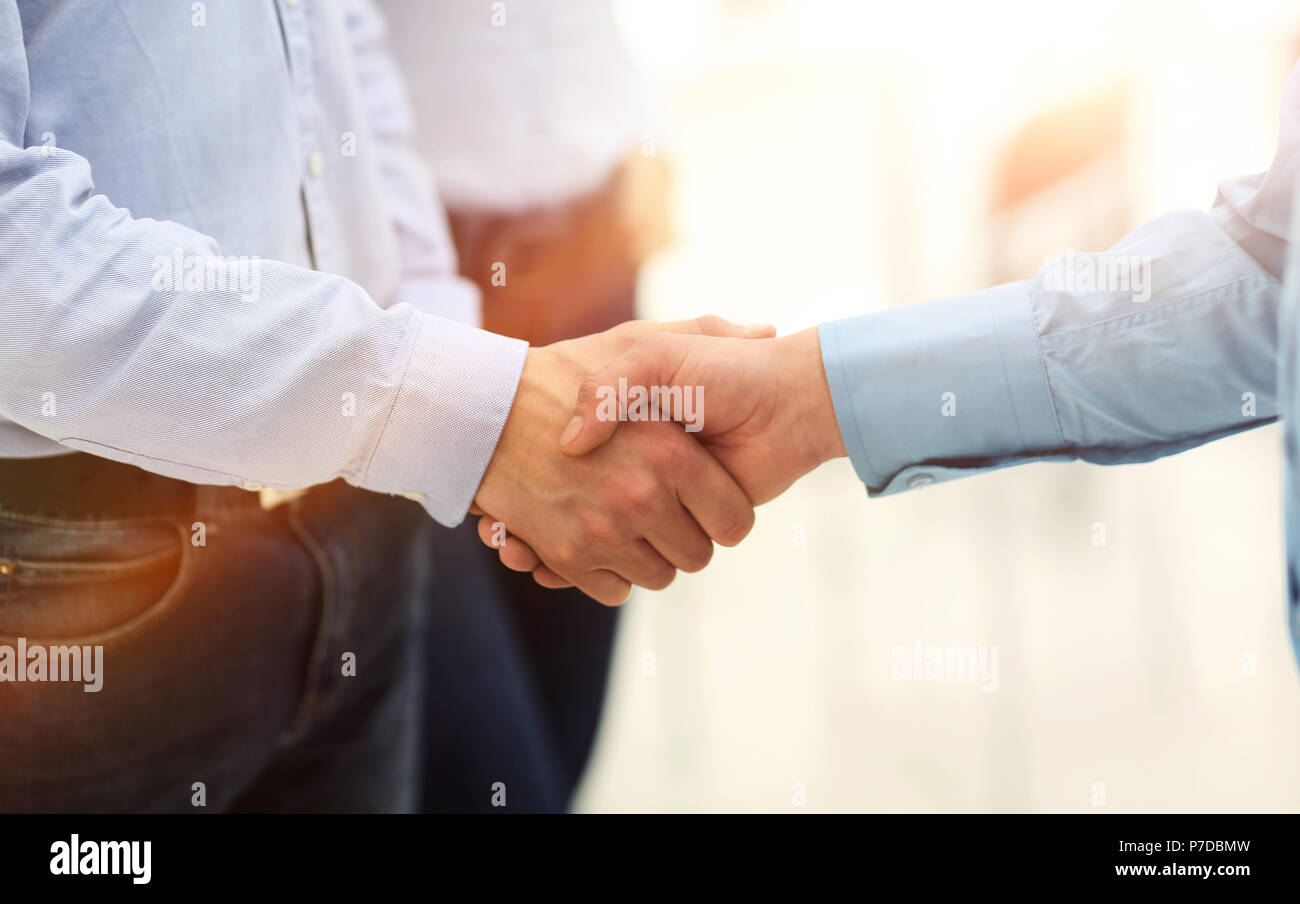 Businessman and a co-worker shaking hands during a meeting. - Stock Image