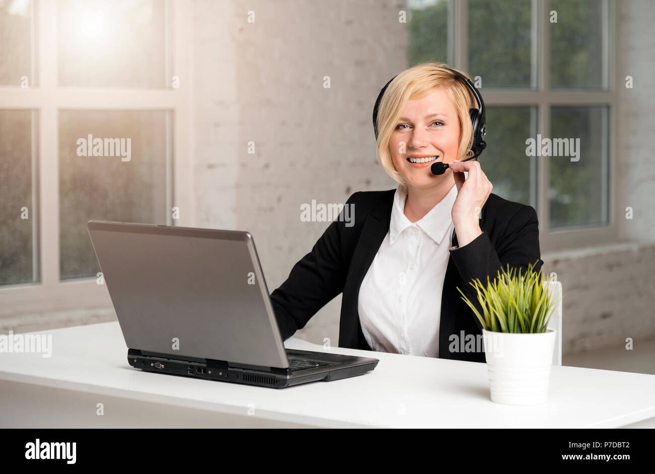 Call center operator, blonde woman dressed in black jacket and white shirt working on laptop via headset in white office Stock Photo