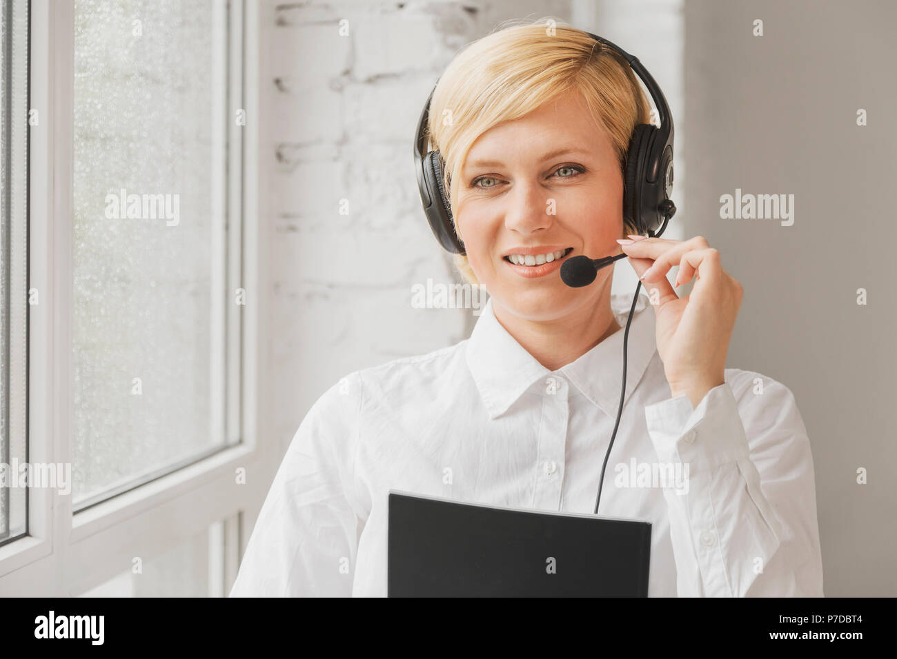 Blonde online consultant woman wears black earphones headset consulting customers standing near rainy window in white office - Stock Image