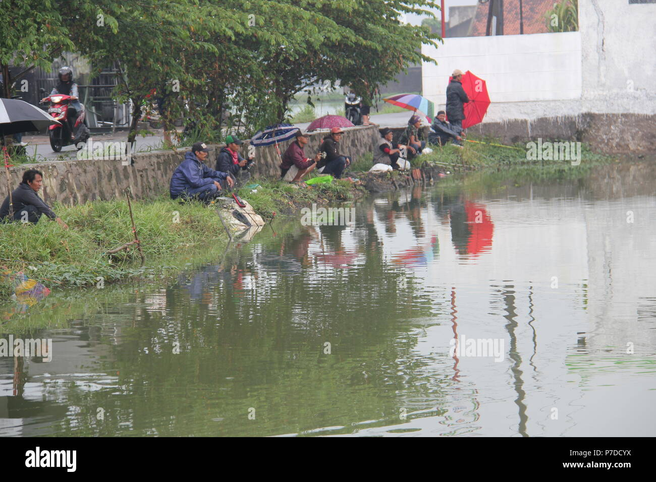 People fishing in a pond near housing in Bandung, Indonesia. - Stock Image