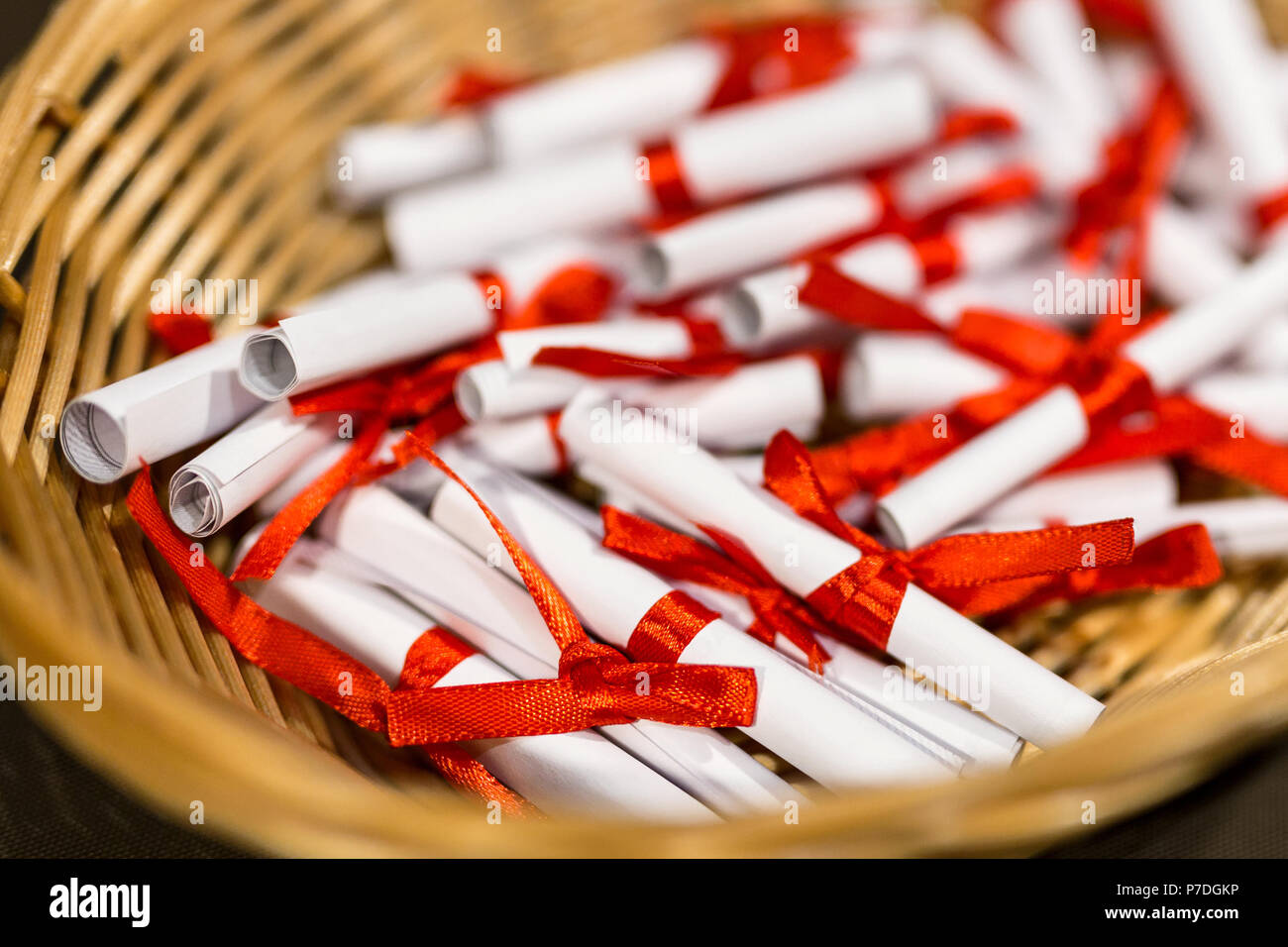 Pile of small paper scrolls in wicked basket.  White scrolls tied with red ribbon. Future prediction, advice or sign concept. - Stock Image