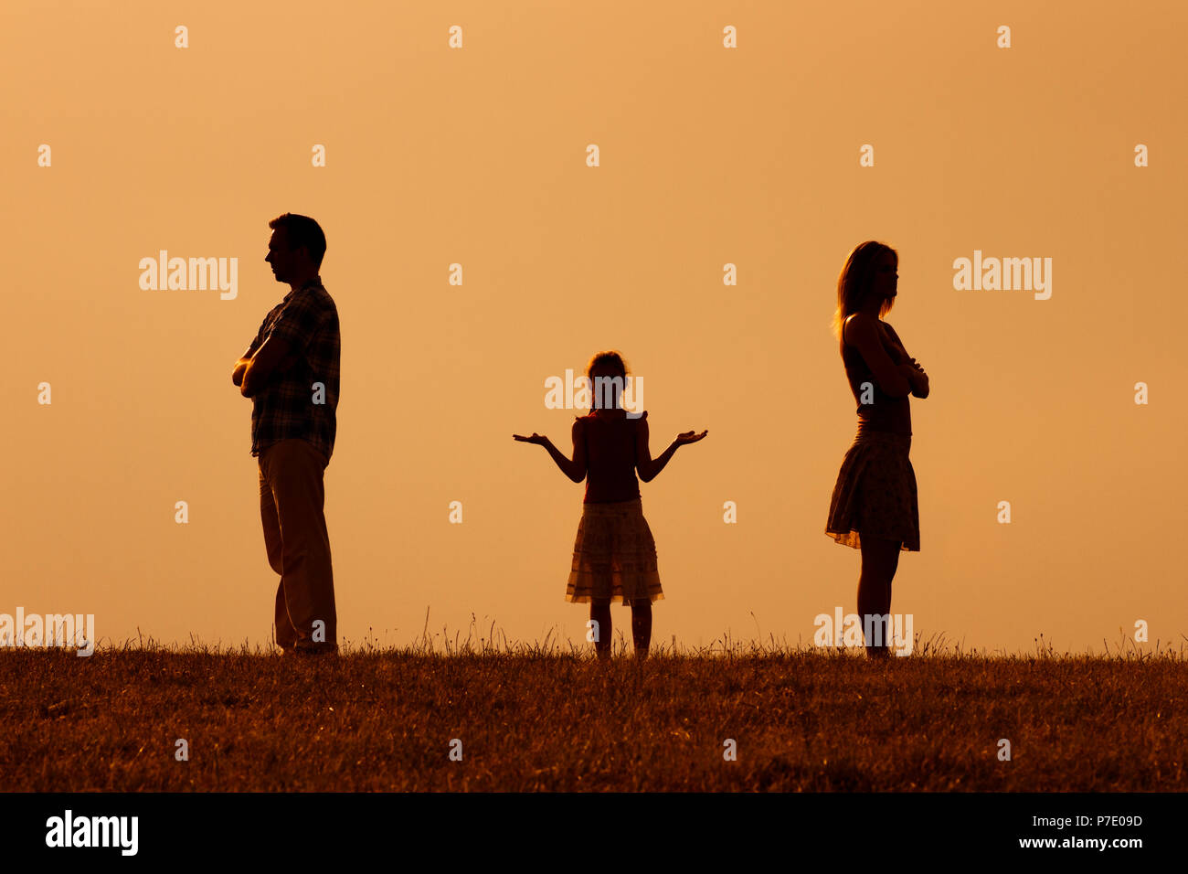 Silhouette of a angry husband and wife on each other with their confused daughter standing in the middle - Stock Image