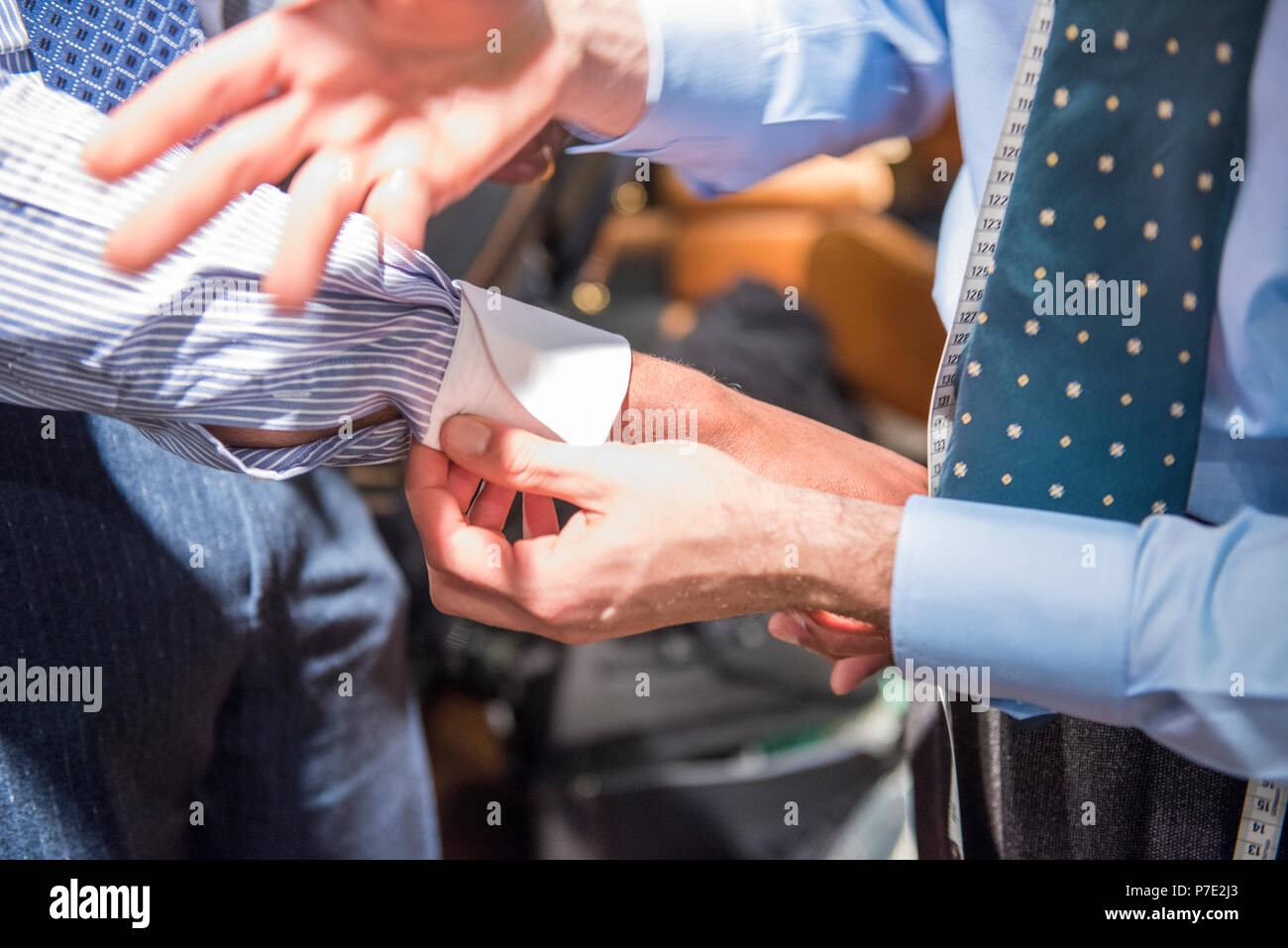 Tailor fastening shirt cuff of customer, cropped close up of hands - Stock Image
