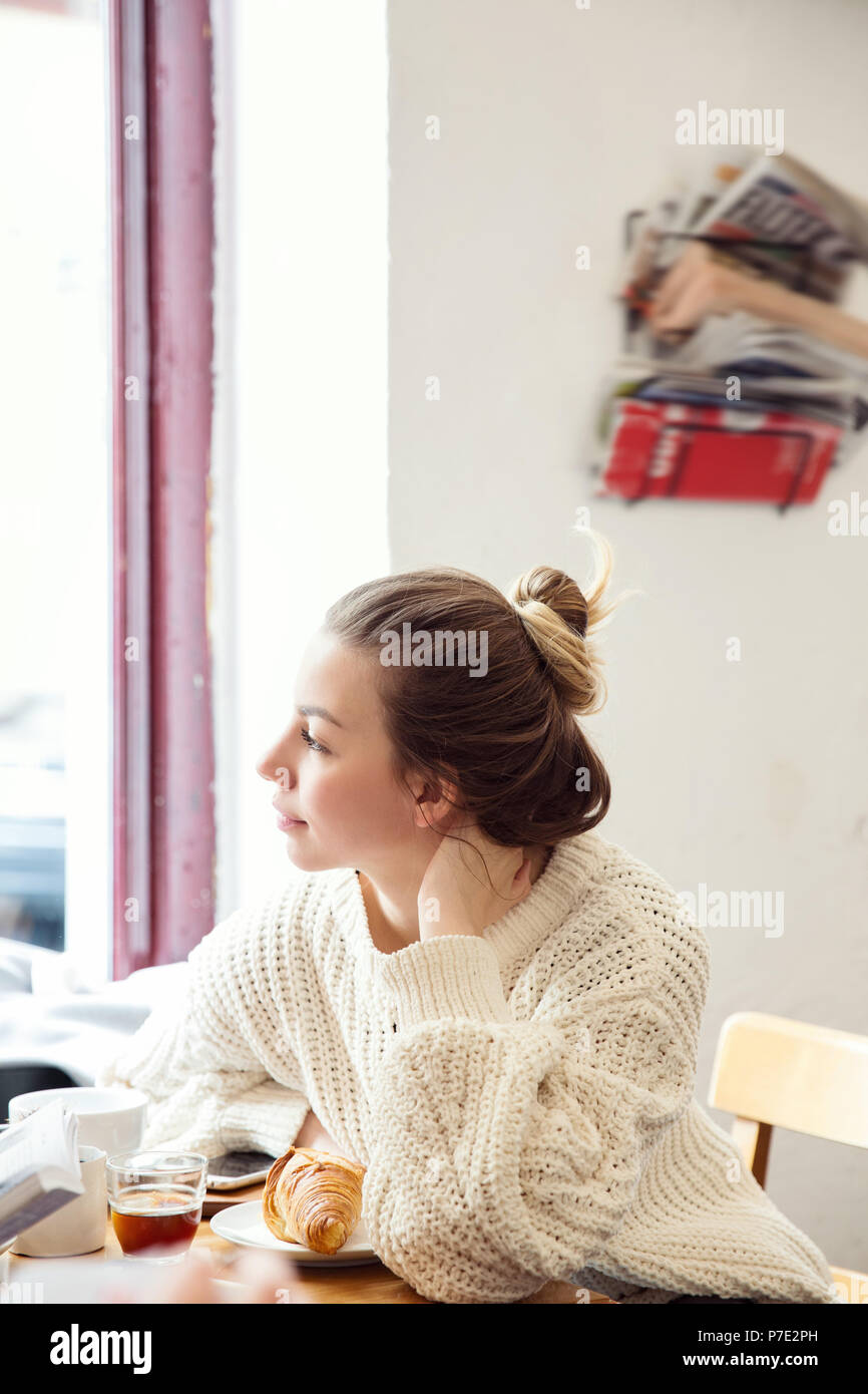 Woman daydreaming in cafe - Stock Image