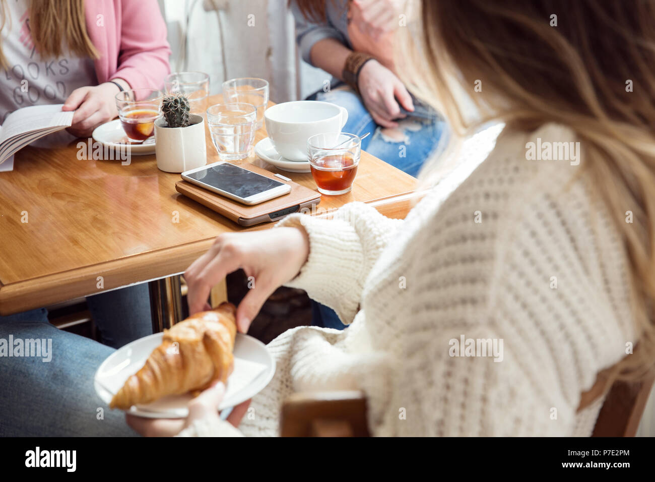 Women chatting over coffee and croissant in cafe - Stock Image