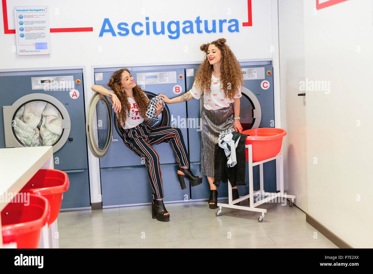 Fashion blogger twins at laundrette - Stock Image