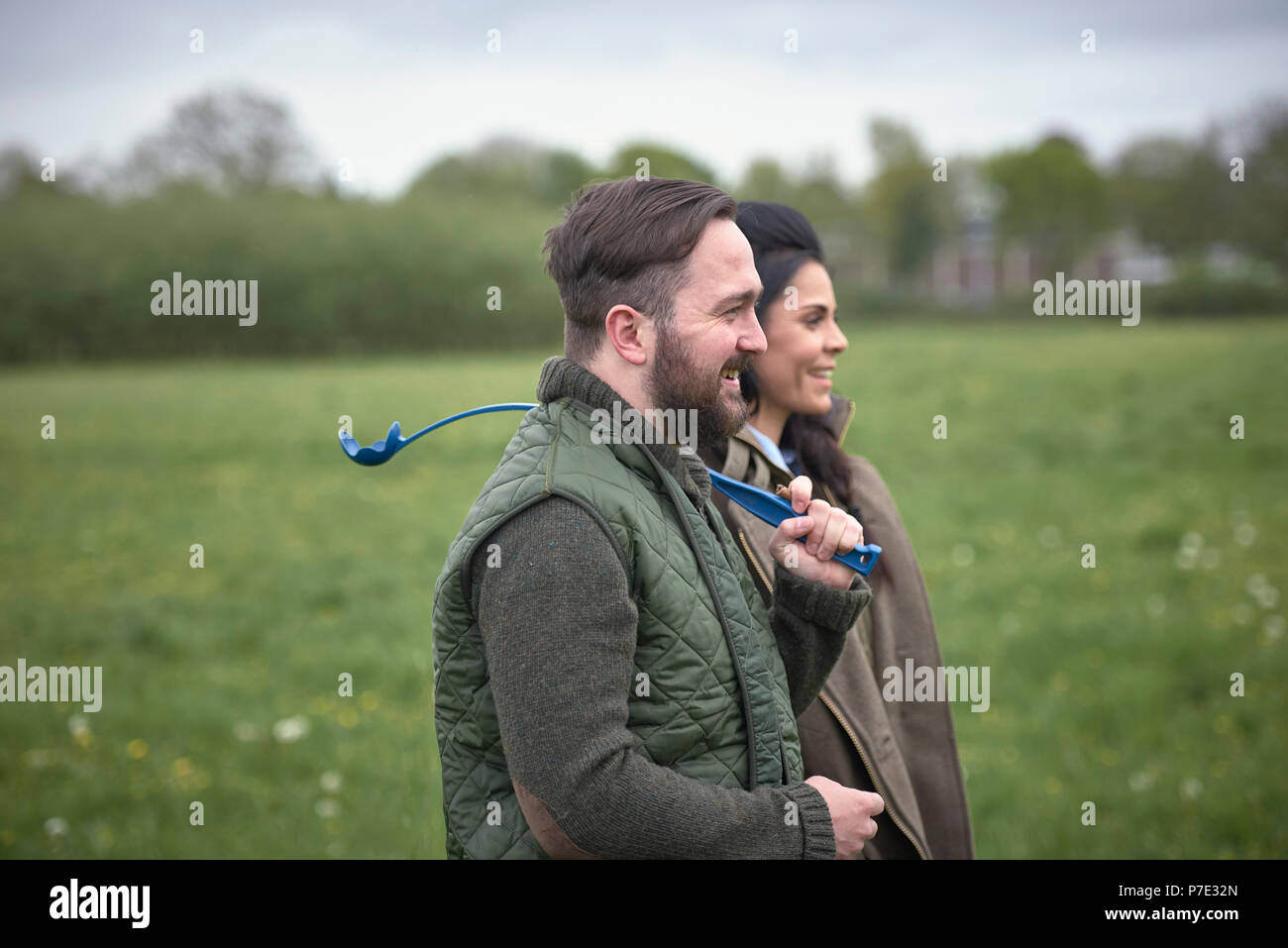 Woman and man dog walking in field - Stock Image