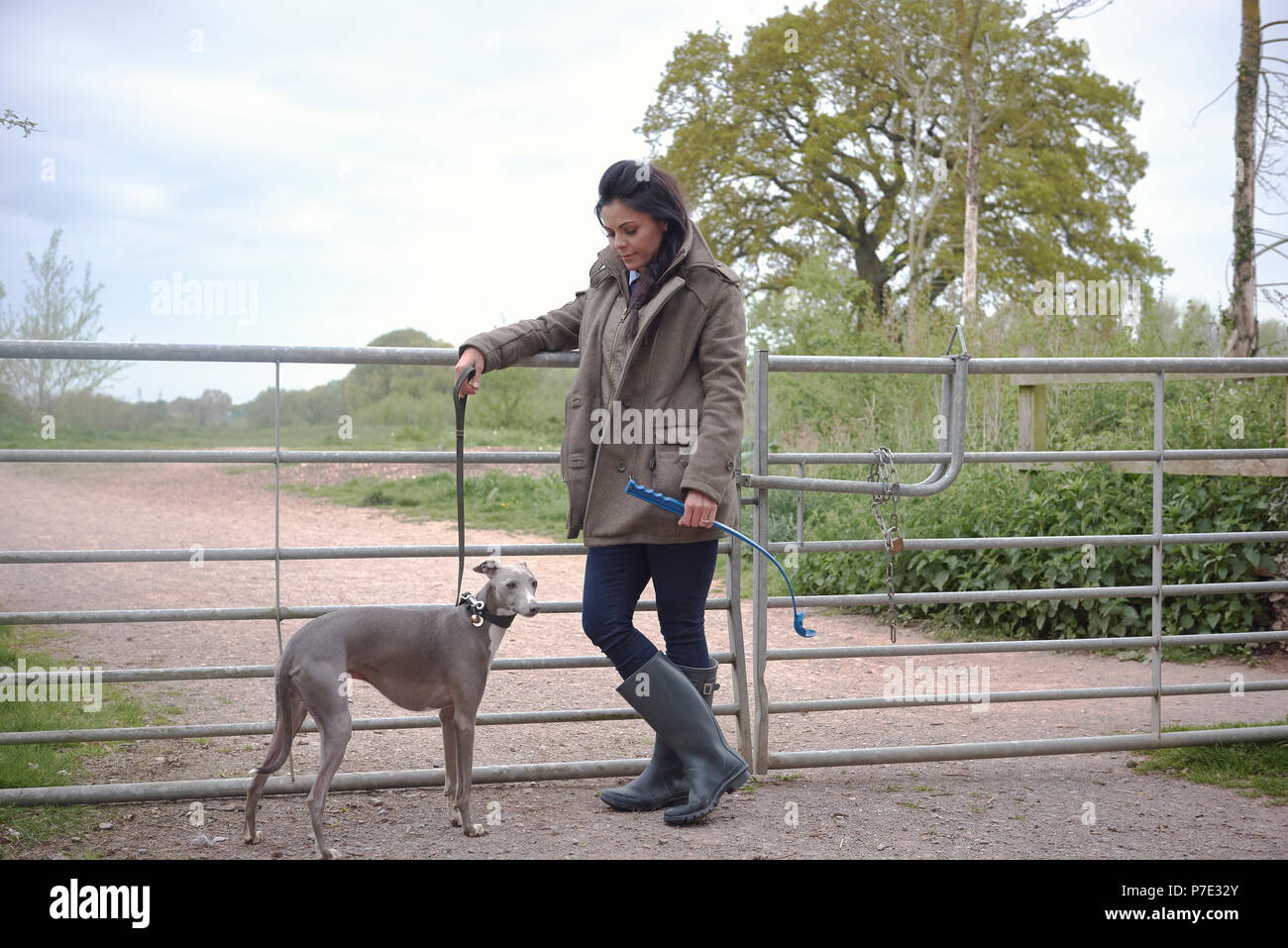 Woman with dog leaning on rural gate - Stock Image