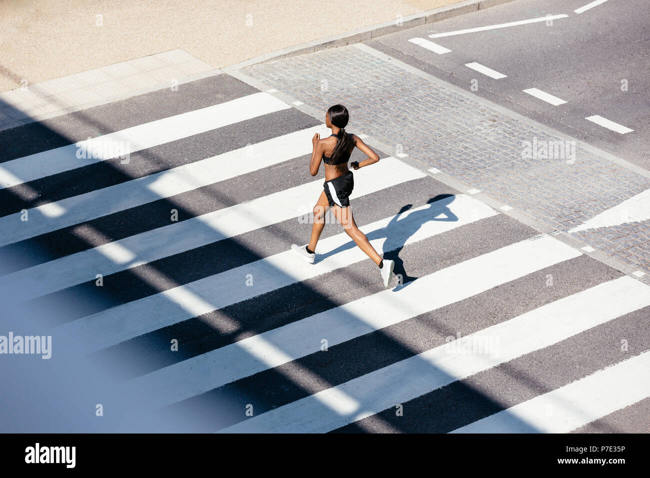 Young woman running on zebra crossing - Stock Image