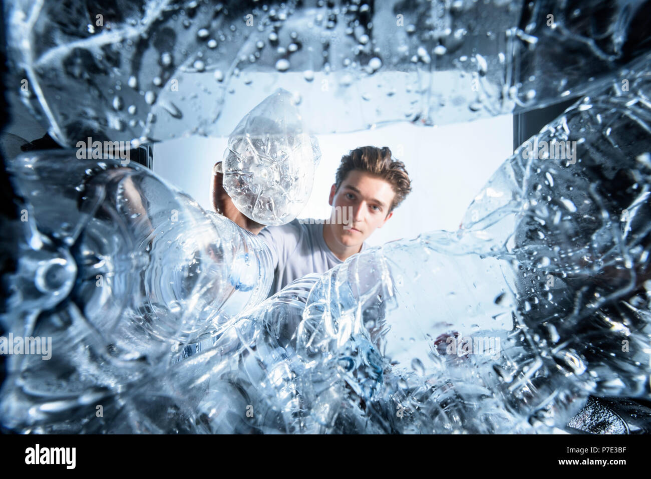 Man throwing away plastic water bottles into recycling bin - Stock Image