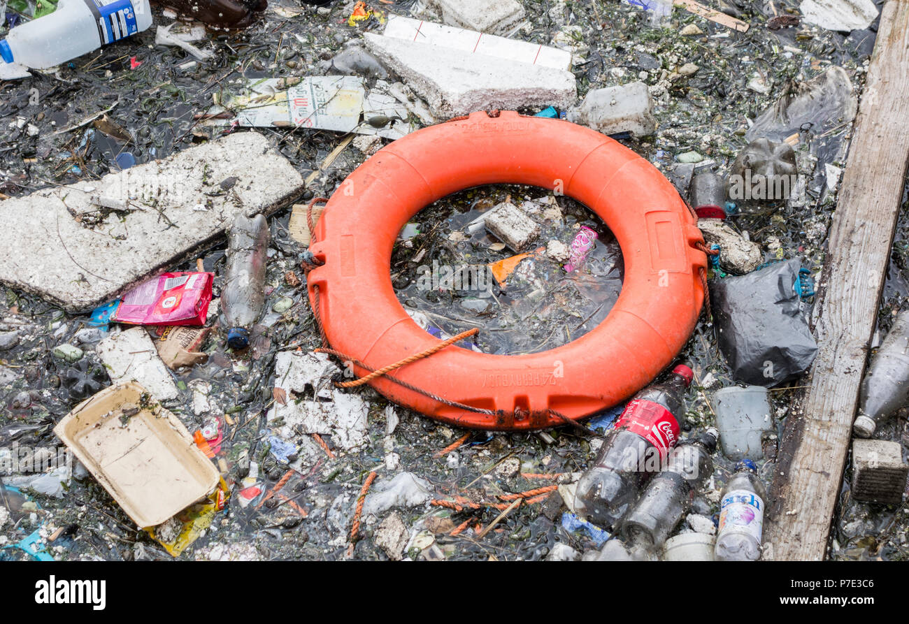 Plastic bottles and rubbish and lifebelt floating in uk river. - Stock Image