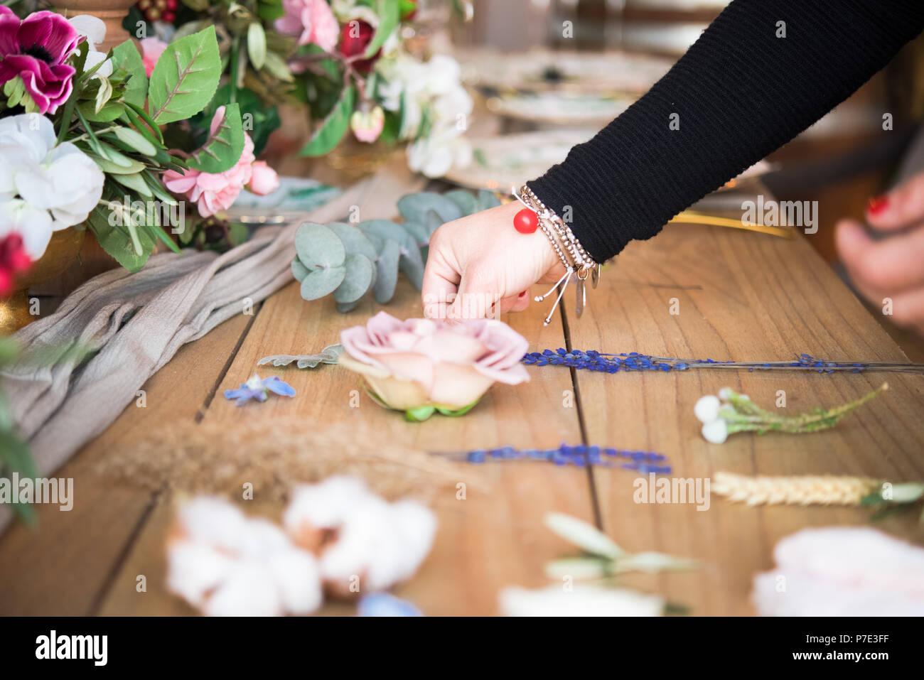 Woman arranging flower head and stems on wooden table, detail of hand Stock Photo