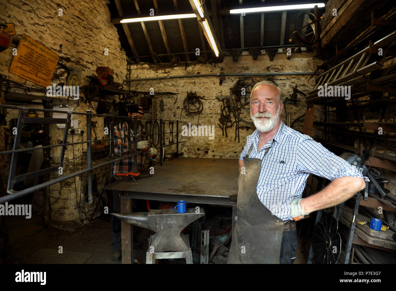 Blacksmith with hands on hips in blacksmiths shop, portrait Stock Photo