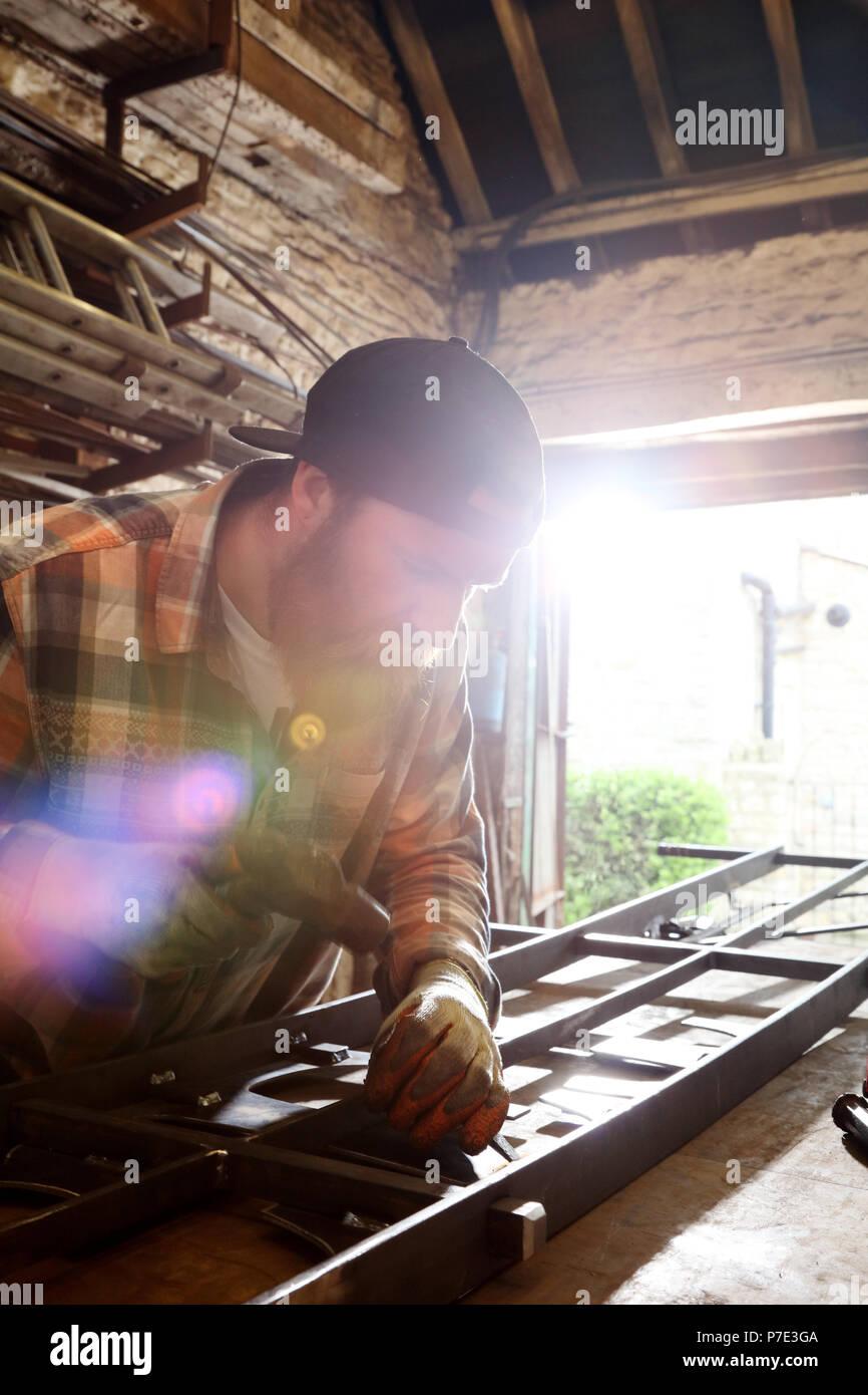 Blacksmith hammering metal on workbench in blacksmiths shop - Stock Image
