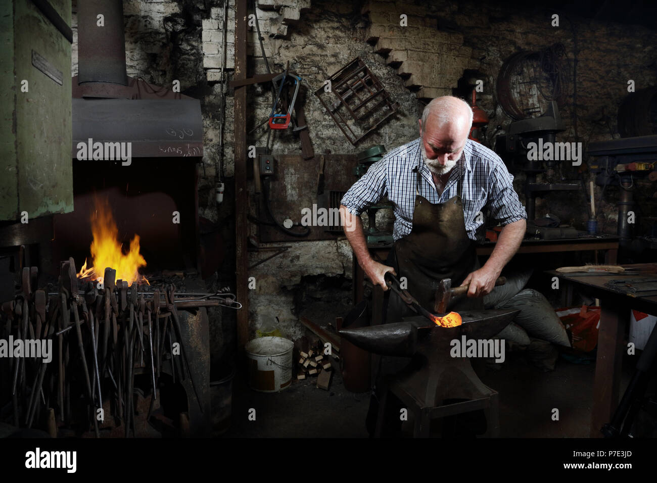 Blacksmith hammering red hot metal in blacksmiths shop - Stock Image
