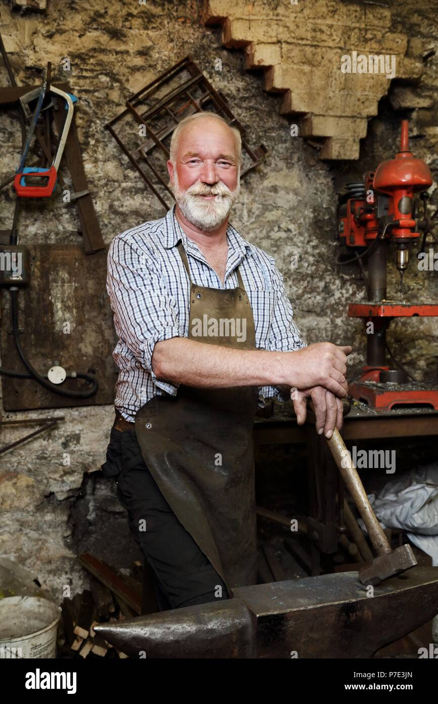 Blacksmith with hammer and anvil in blacksmiths shop, portrait - Stock Image