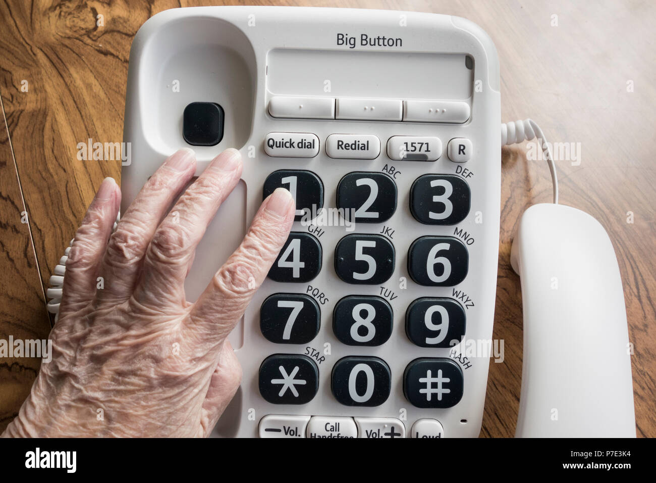 Visually impaired elderly woman dialling NHS 111 help line on big button telephone. Stock Photo