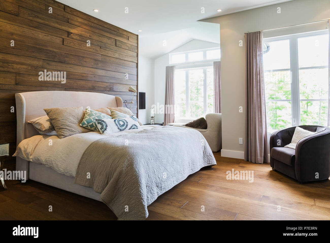 King size bed in bedroom with hickory wood floorboards - Stock Image