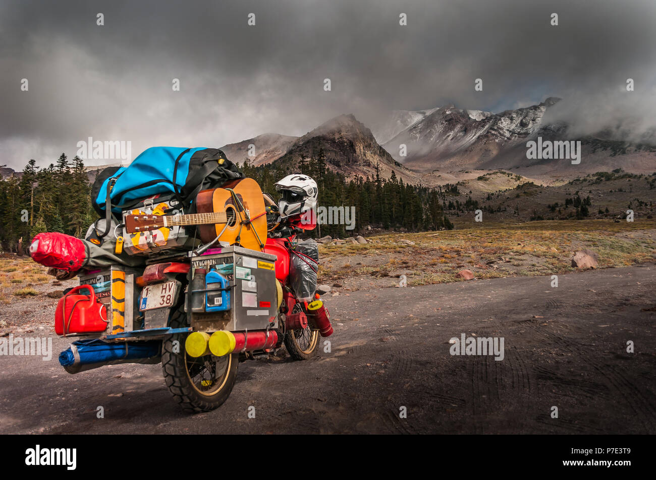 Loaded touring motorcycle on roadside with dramatic sky over Mount Shasta, California, USA - Stock Image