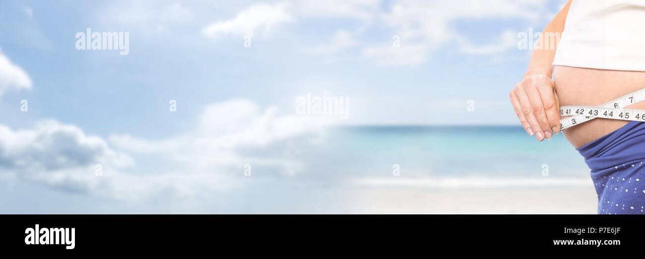 Woman measuring weight with measuring tape on waist on Summer beach with transition - Stock Image