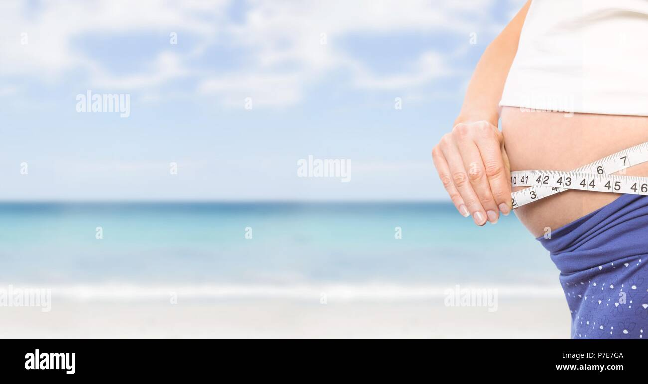 Woman measuring weight with measuring tape on waist on Summer beach - Stock Image
