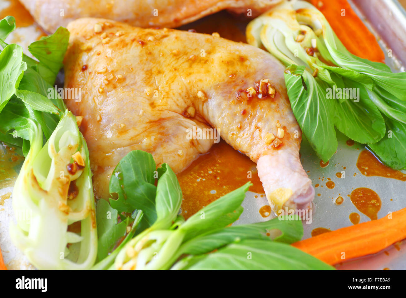 Raw chicken with hoisin garlic sauce, carrots and baby bok choy - Stock Image