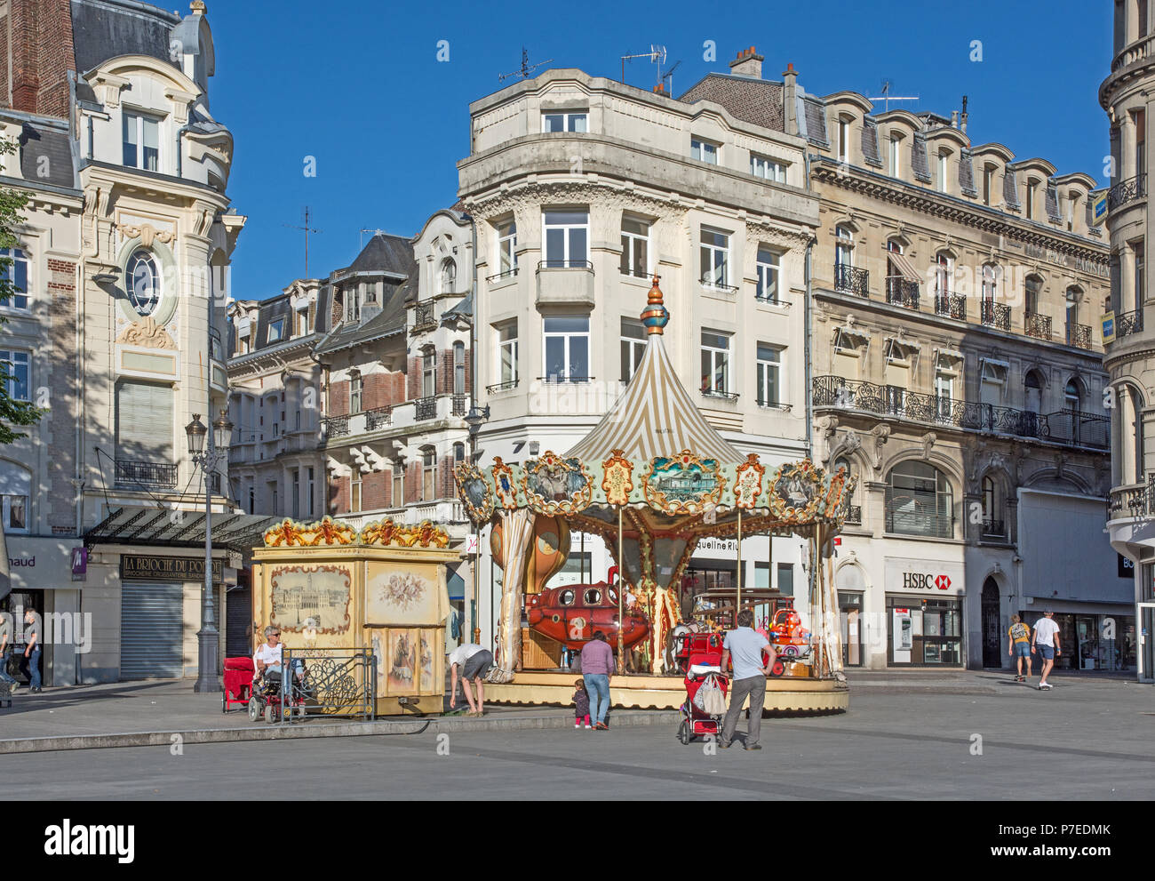 Charming old fashioned traditional carousel children's roundabout in Place de l'Hotel de Ville St Quentin Aisne France Stock Photo