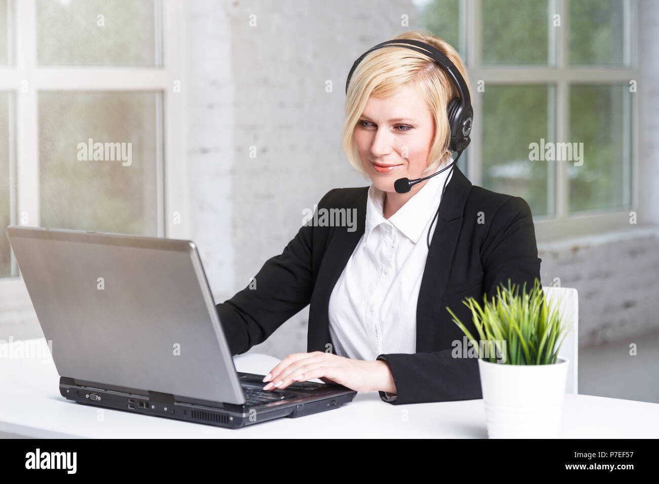 Beautiful blonde adult woman call center operator dressed in black stylish suit working in white office on table with laptop Stock Photo