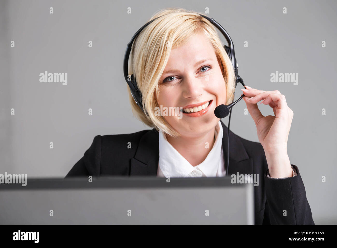 Pretty smiling blonde woman, call center operator dressed in black stylish suit with headset earphones Stock Photo