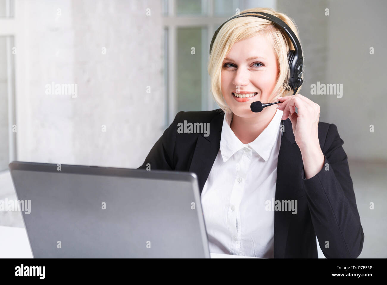 Portrait of beautiful smiling blonde woman, call center operator dressed in black stylish suit with headset earphones working in white office - Stock Image