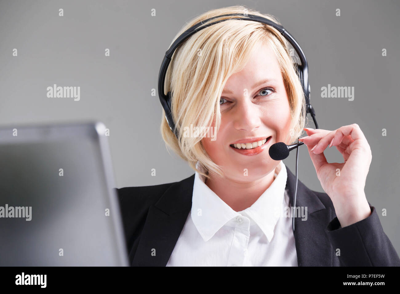 Smiling woman, call center operator dressed in black stylish suit with headset earphones - Stock Image