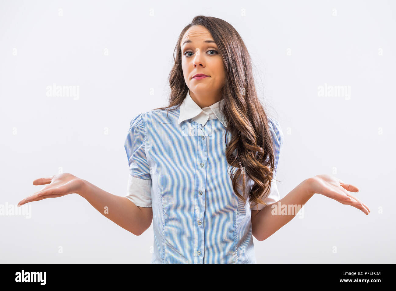 Image of confused businesswoman shrugging on gray background. - Stock Image