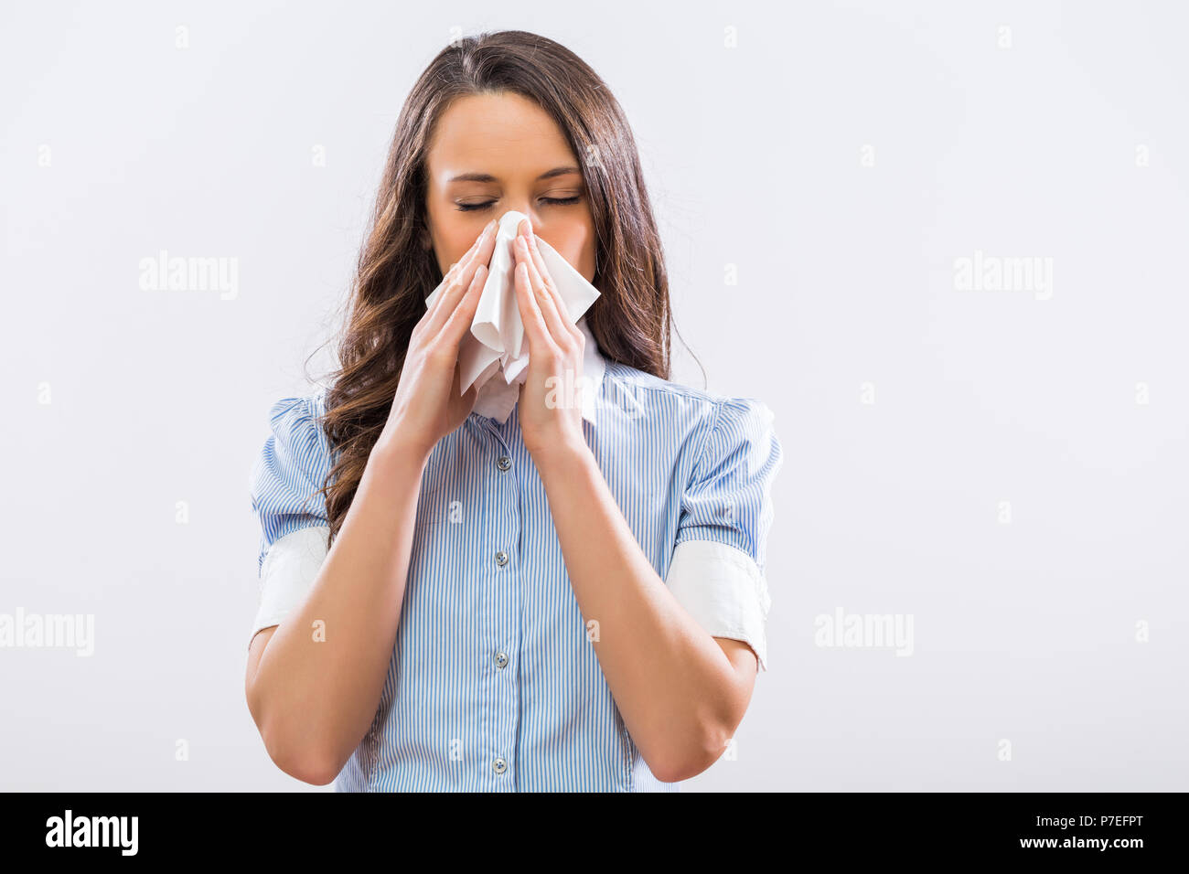 Image of businesswoman blowing nose on gray background. - Stock Image