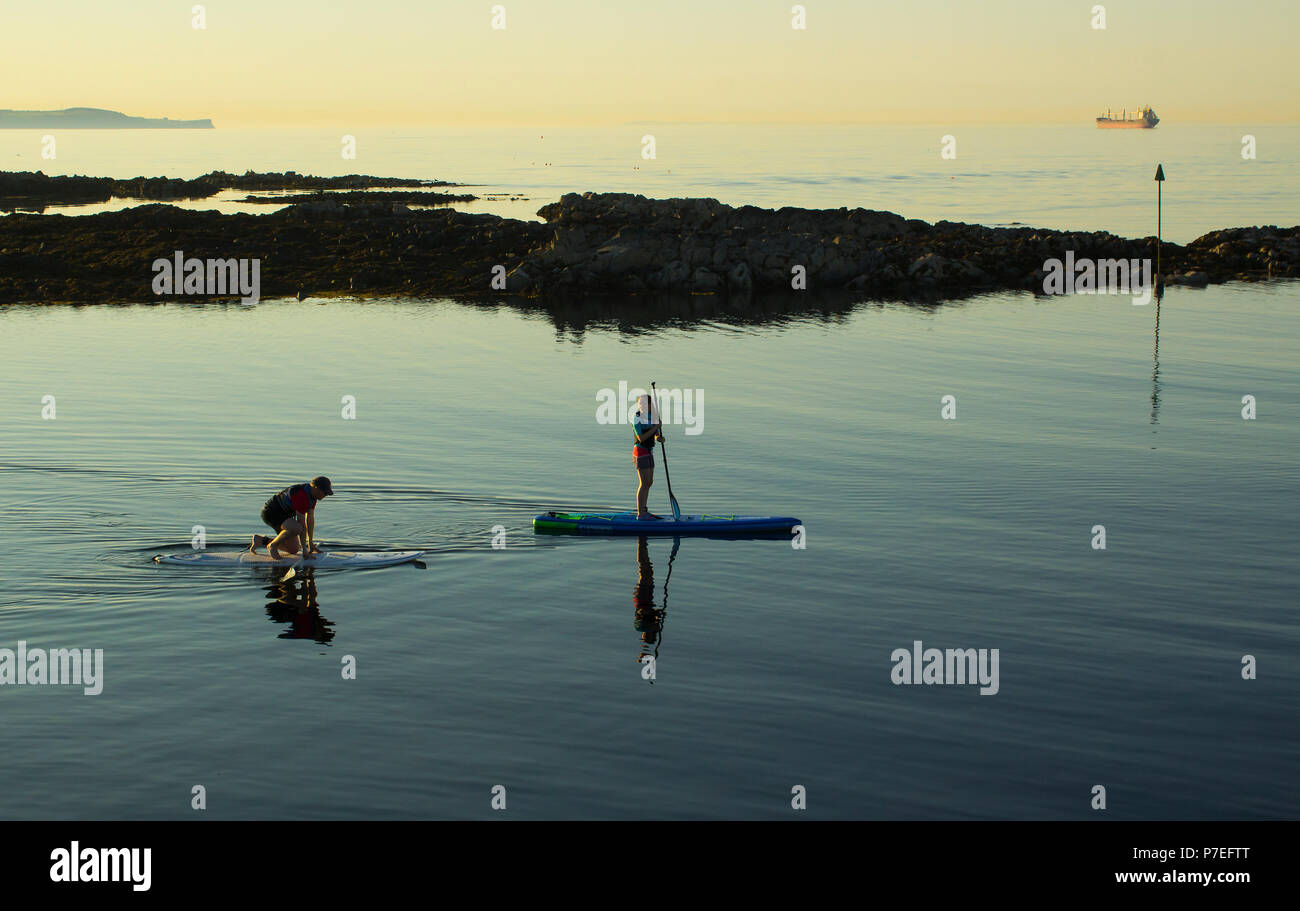 29 June 2018 A couple slowly paddle their surf boards in the calm sea at Groomsport harbour near Bangor Northern Ireland on a calm and warm summer eve - Stock Image