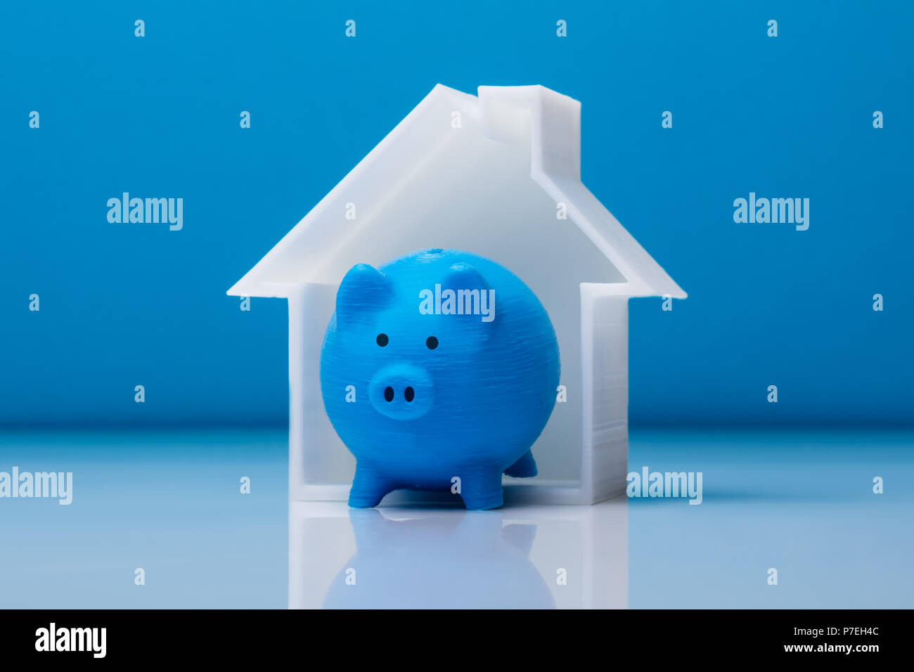 Close-up Of Piggybank And House Model In Front Of Blue Background - Stock Image