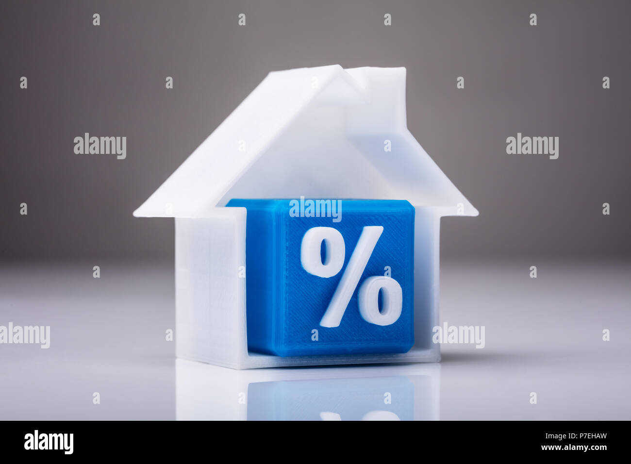 Blue Cube With Percentage Sign Inside House Model On Reflective Background - Stock Image