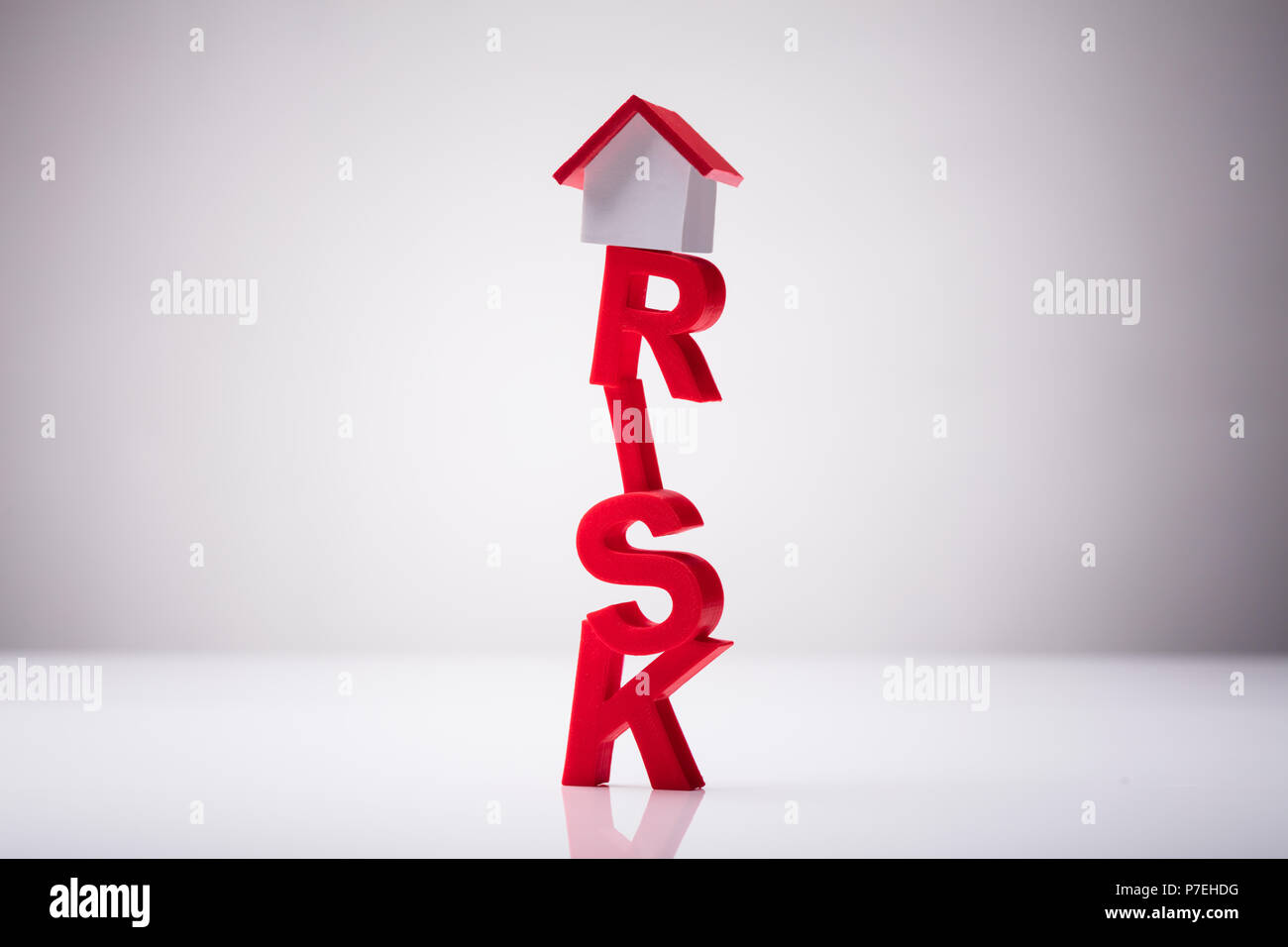 Small House Model Over Risk Word Against White Background Stock Photo