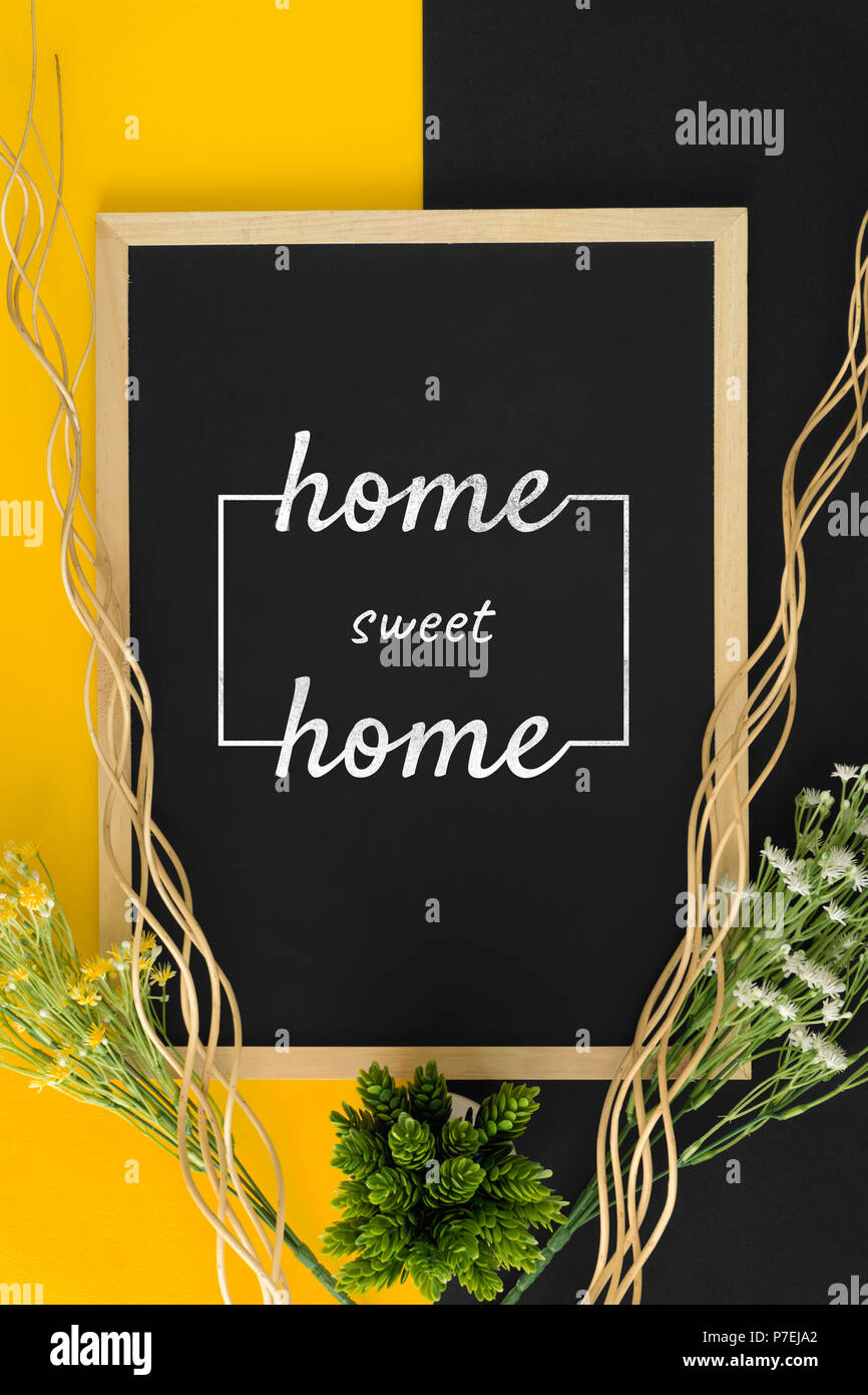Home sweet home on black and yellow background with rustic wood sticks and flower. - Stock Image