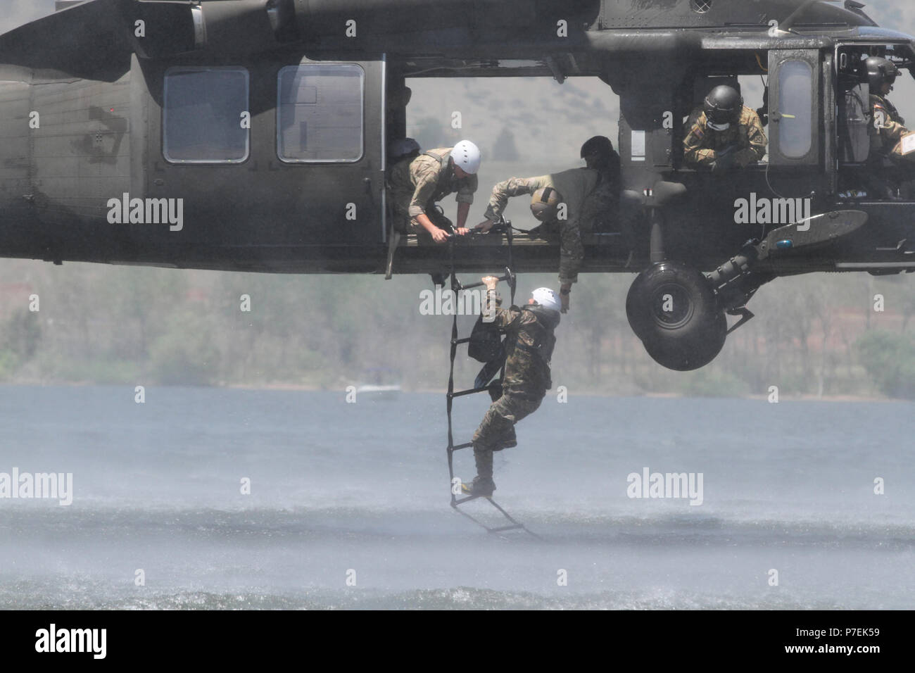 A soldier from 10th Special Forces Group (Airborne) climbs a ladder during water extraction training on Chatfield Reservoir near Littleton, Colo., June 29, 2018. This waterborne training event gave green berets the opportunity to train on unconventional infiltration and exfiltration tactics, thereby sharpening the unit's ability to operate on land, sea, and air. - Stock Image