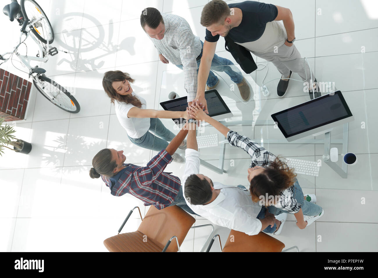 creative team with hands clasped together. - Stock Image