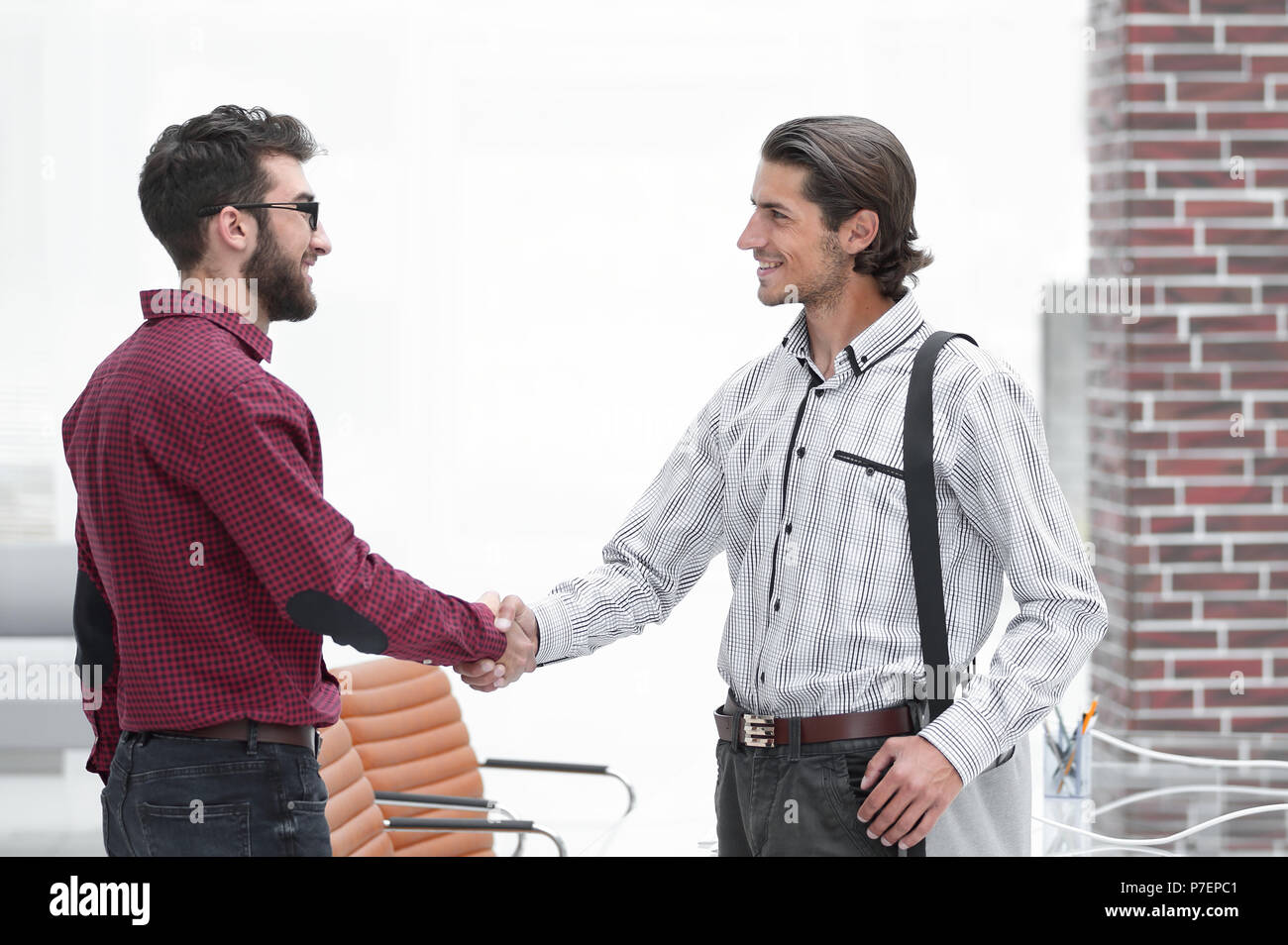handshake two employees standing in the office - Stock Image