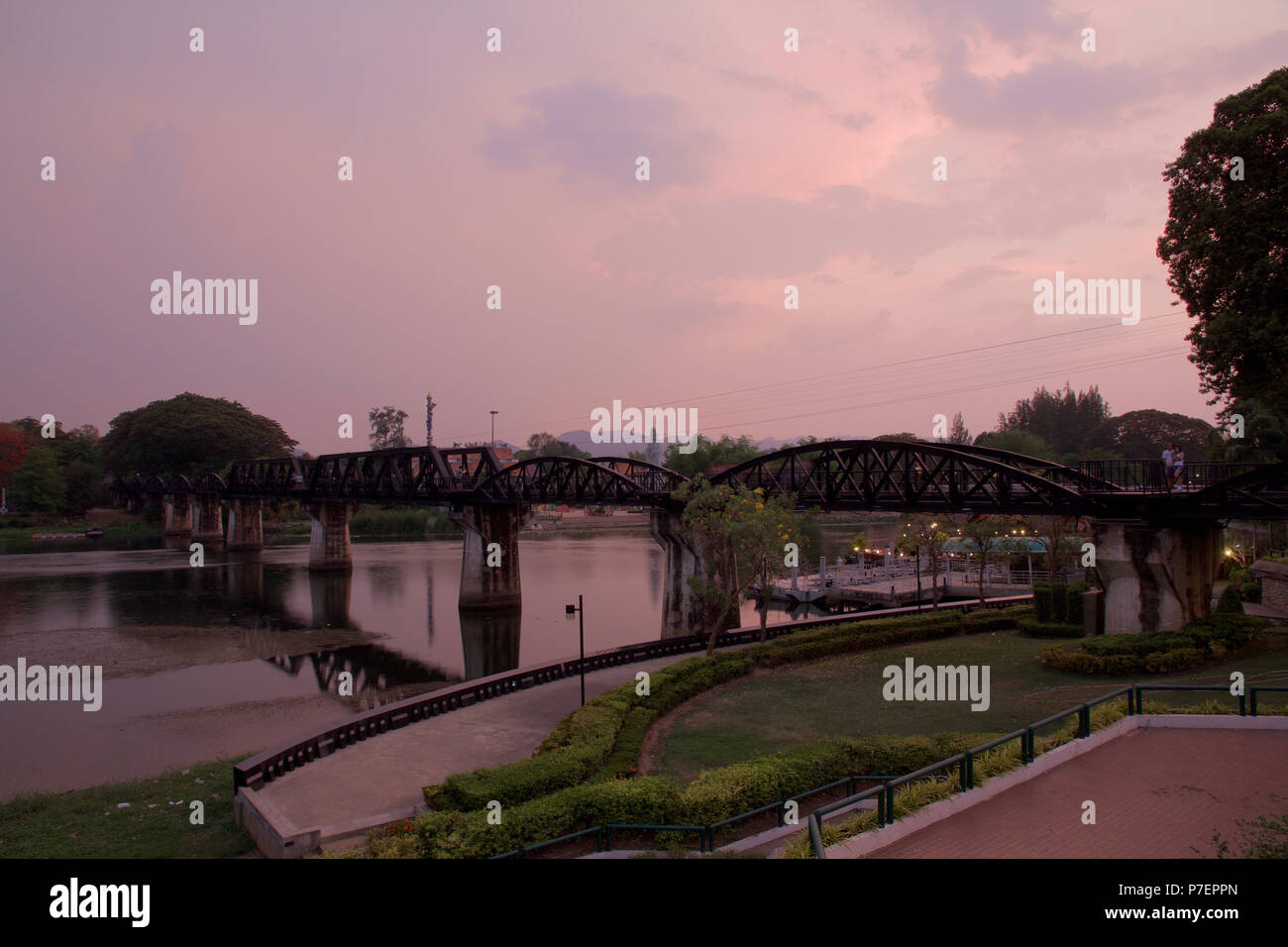 Kanchanaburi, Thailand - April 9, 2016: Tourists on the Bridge over The River Kwai after sunset - Stock Image