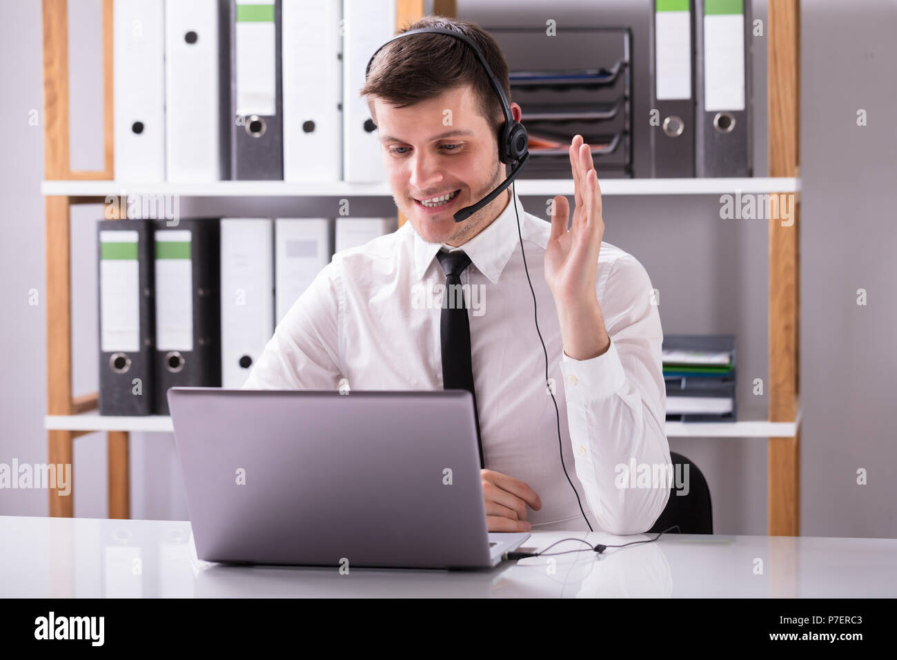 Young Businessman Using Headphone While Working On Laptop At Workplace Stock Photo